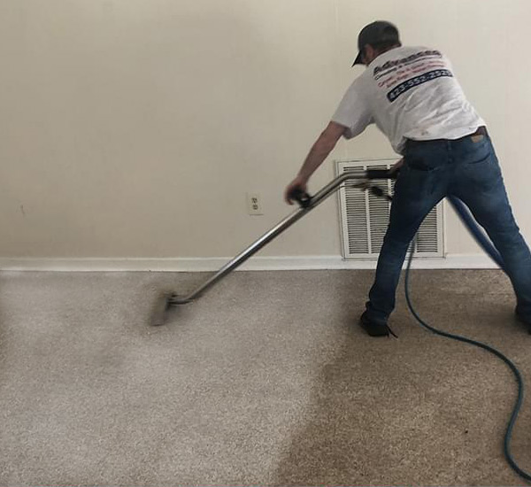 Employee of Advanced Cleaning & Restoration cleaning a very soiled carpet