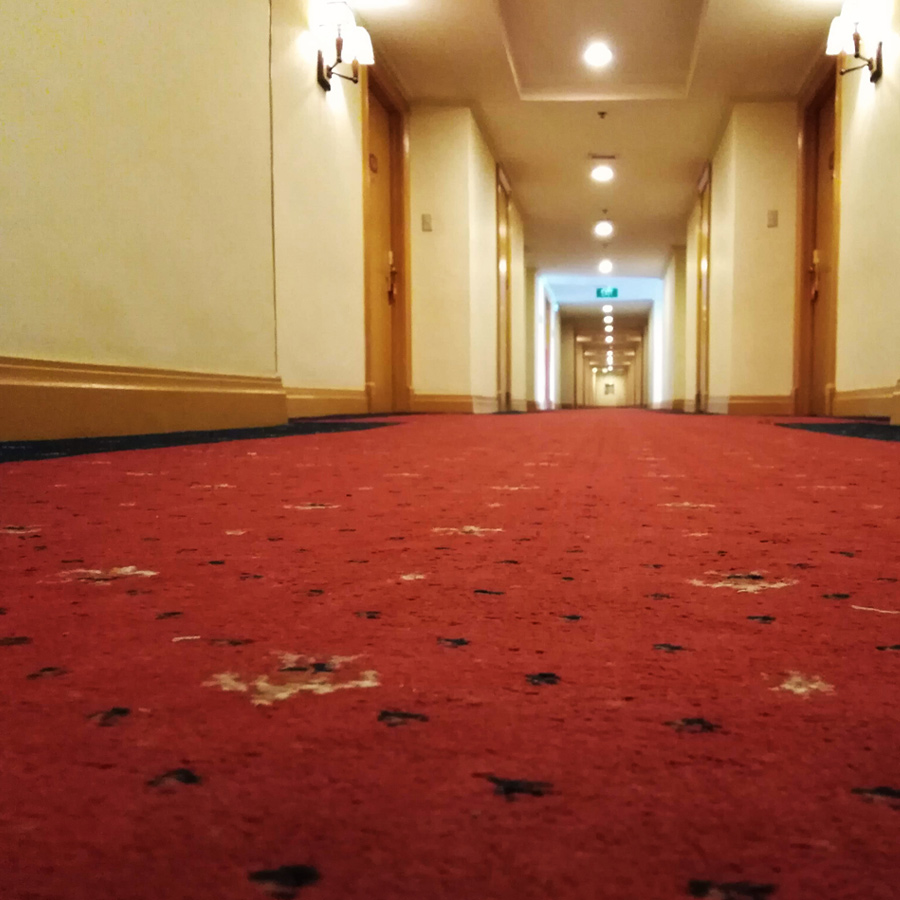 Hotel carpet after professional carpet cleaning job hallway stretching into distance