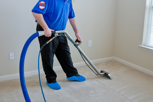 Man cleaning a residential carpet with commercial steam cleaning equipment